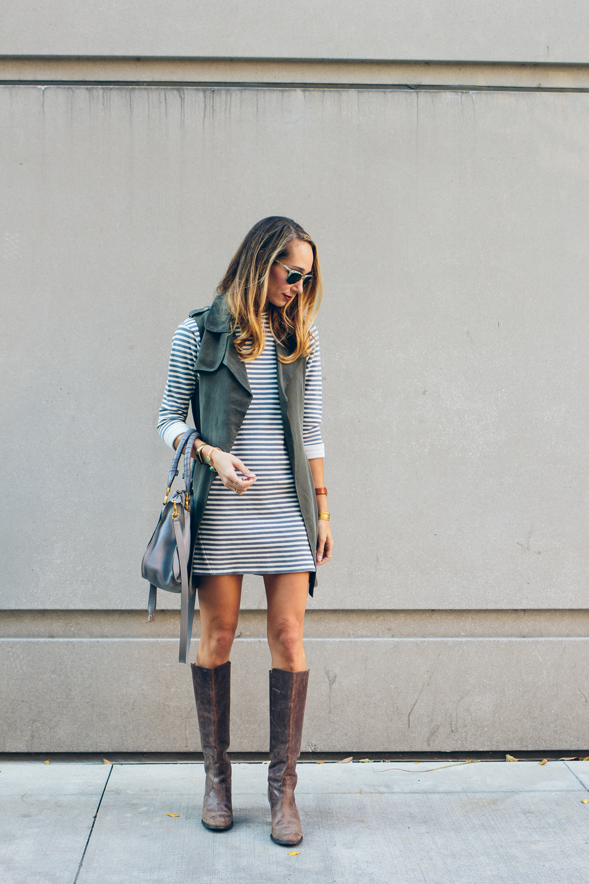 striped dress, trench vest, leather boots, chloe bag — via @TheFoxandShe