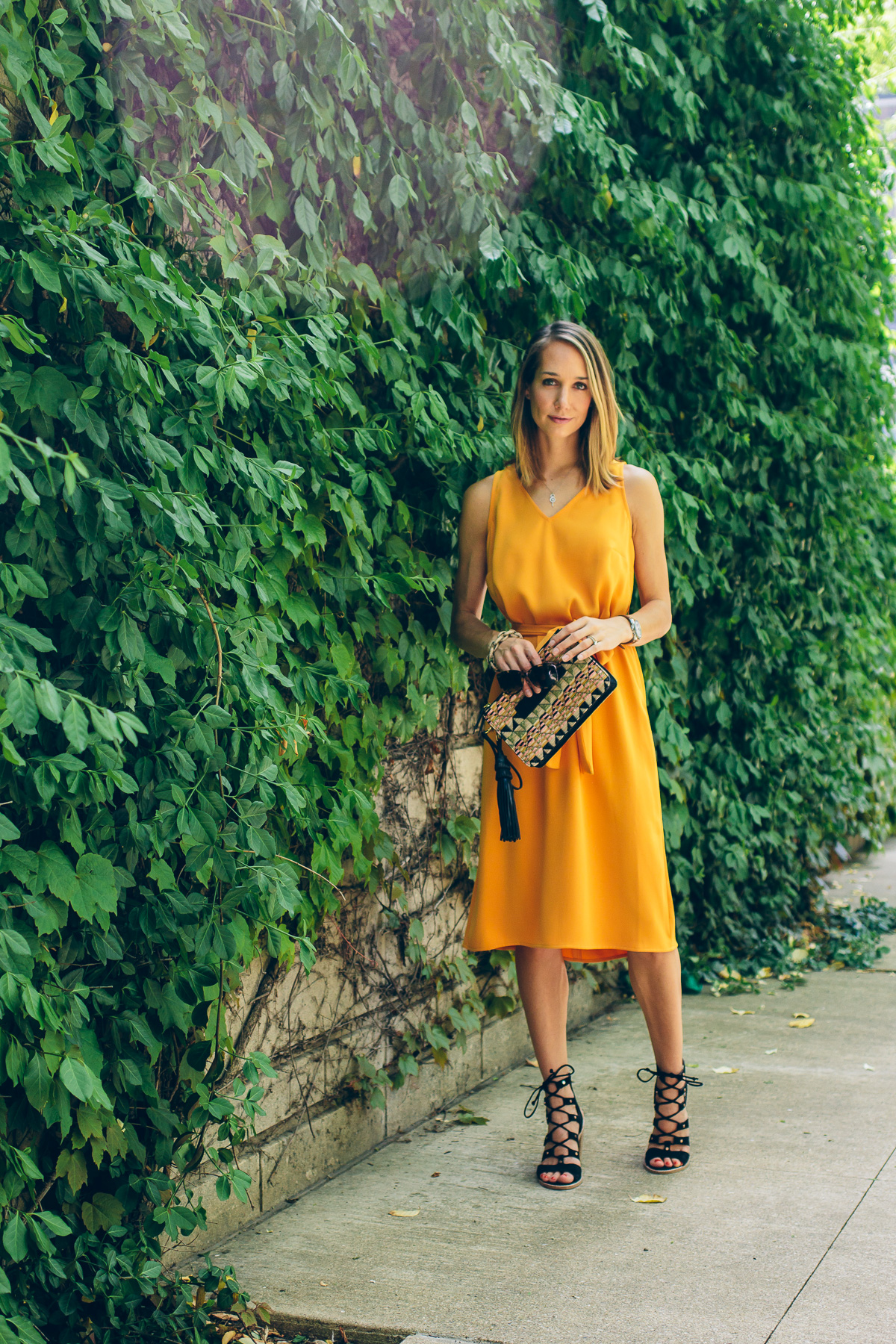 yellow tie dress with straw tassel clutch and lace up heels
