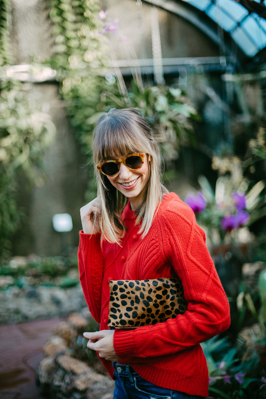 red sweater and leopard clutch