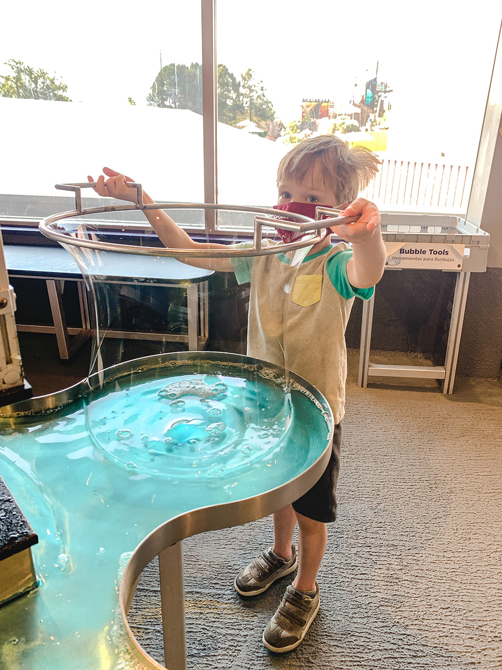 kid playing with large bubbles